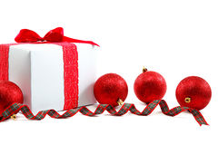 White gift box with red ribbon and christmas balls around. Royalty Free Stock Photography