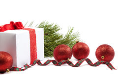 White gift box with red ribbon and christmas balls around. Royalty Free Stock Image