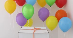 White gift box with red ribbon and colorful balloon. On white background stock video