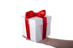 White gift box with red ribbon in hand Stock Images