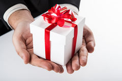 White gift box with red ribbon in hand Stock Photography