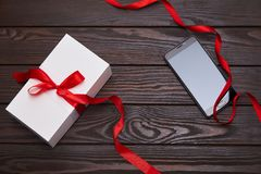 White gift box with red ribbon and smartphone on a wooden background stock photo
