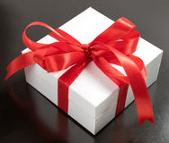 White gift box with red ribbons isolated on black background Royalty Free Stock Photo