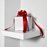 White gift box with a red satin ribbon Royalty Free Stock Image