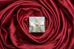 White gift box on red silk Stock Photos