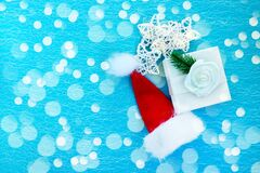 White gift box, Santa hat and Christmas decorations on a blue background. Christmas and New Year background. Christmas and New Yea