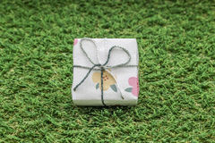 white gift box with silver ribbon on green grass background Royalty Free Stock Image