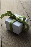 White Gift Box with Soft Green Ribbon on Old Wood Table Royalty Free Stock Photos