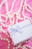 White gift box surrounded by pearl necklace on pink wooden background. Concept of Women`s day gift Royalty Free Stock Image