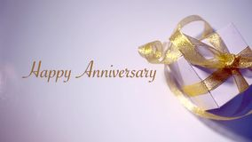 The white gift box is tied with gold ribbon, accompanied by happy anniversary writing. Isolated on white background and lighting stock video footage