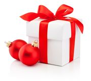 White gift box tied red ribbon bow and two Christmas bauble Isolated on white background. White gift box tied red ribbon bow and two Christmas bauble Isolated on royalty free stock images
