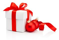 White gift box tied red ribbon bow and two Christmas baubles Iso royalty free stock images