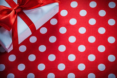 White gift box with tied ribbon on polka-dot red fabric celebrat Royalty Free Stock Image