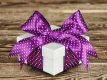 White gift box with a violet bow on the old board stock photos
