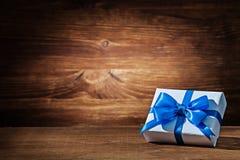 Free White Gift Box With Blue Ribbon On Vintage Wood Stock Image - 141548331
