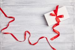 White gift box wrapped with red ribbon on a wooden background stock image