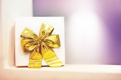 Gift box with a yellow bow on a purple background stock image