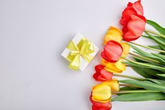 White gift box with yellow ribbon. Near bouquet yellow red tulip on white background. Flat lay. Mother or Woman  Day. Greeting Card. Copy space. Spring Stock Photos
