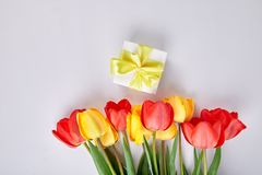White gift box with yellow ribbon. Near bouquet yellow red tulip on white background. Flat lay. Mother or Woman  Day. Greeting Card. Copy space. Spring Stock Photo