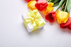 White gift box with yellow ribbon. Near bouquet yellow red tulip on white background. Flat lay. Mother or Woman  Day. Greeting Card. Copy space. Spring Stock Images