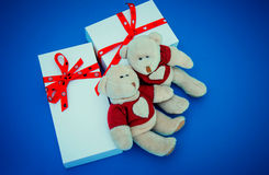 White gift boxes and bears on blue background. Two white gift boxes and two bears on blue background Royalty Free Stock Photography