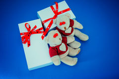 White gift boxes and bears on blue background. Two white gift boxes and two bears on blue background Stock Image