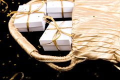 White gift boxes with gold ribbon pop out from golden bag on shine background. Close up. White gift boxes with gold ribbon pop out from golden bag on shine Royalty Free Stock Photography