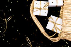White gift boxes with gold ribbon pop out from golden bag on shine background. Flat lay.  Royalty Free Stock Image