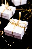 White gift boxes with gold ribbon on shine background. Close up. White gift boxes with gold ribbon on shine background. Close up Stock Image