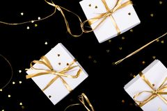 White gift boxes with gold ribbon on shine background. Flat lay.  Royalty Free Stock Photo