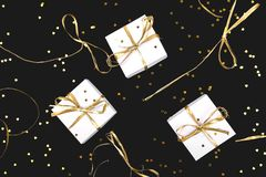 White gift boxes with gold ribbon on shine background. Flat lay royalty free stock images