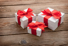 White gift boxes with red bows on the old board. gift concept Stock Images