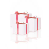 White gift boxes with red ribbon bows, isolated on white. Stock Images