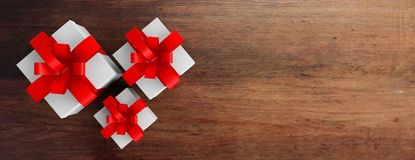 Gifts with red ribbons on wooden background, copy space. 3d illustration Royalty Free Stock Photography
