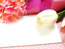 White gift card and tulip artificial flower bouquet with pink background Stock Photo
