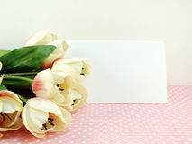 White gift card and tulip artificial flower with pink background Stock Photo