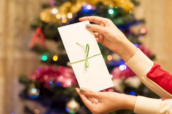 White gift envelope in a female hand with Christmas tree with or Royalty Free Stock Photography