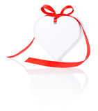 White gift in form heart with bow of red ribbon Stock Images
