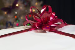 White gift. With red ribbon blurred christmas lights stock image