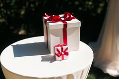 White gift with red ribbon on white table. Outdoor shot in sun light Royalty Free Stock Photos