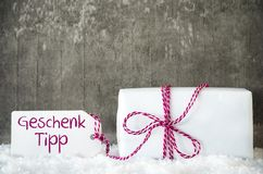 White Gift, Snow, Label, Geschenk Tipp Means Gift Tip. One White Gift With Label With German Text Geschenk Tipp Means Gift Tip. Gray Grungy Cement Background royalty free stock image