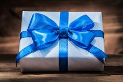 White giftbox with blue ribbon on vintage wood stock photography