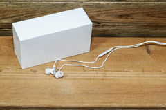 White gifts and white earphone. White gifts and white earphone on old wooden Royalty Free Stock Image