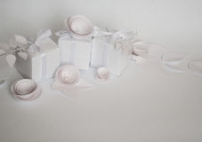 White gifts and white paper flowers. On the white background Stock Image