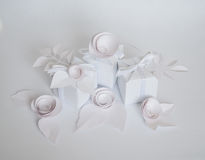 White gifts and white paper flowers. On the white background Royalty Free Stock Images