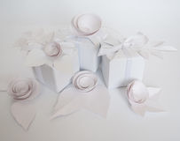White gifts and white paper flowers. On the white background Stock Photo