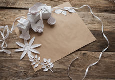 White gifts and white paper flowers. On the wooden background Royalty Free Stock Images