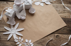 White gifts and white paper flowers. On the wooden background Stock Image