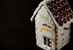 White gingerbread house with a brown roof, a window and the inscription happy New Year on a white wall stock photo