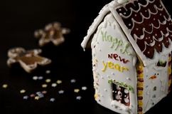White gingerbread house with a brown roof, a window and the inscription happy New Year on a white wall royalty free stock photo